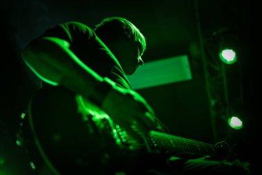 Guitar player in green light