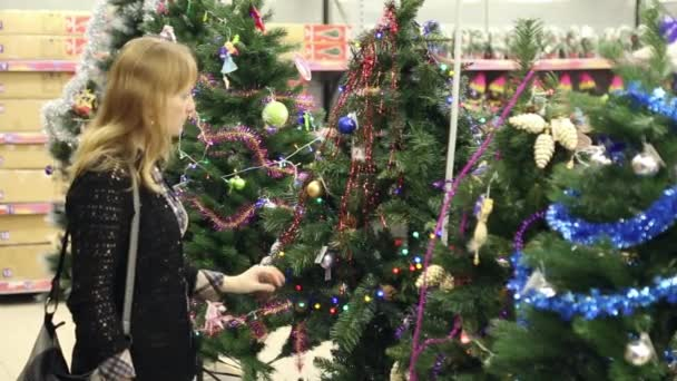 The girl chooses artificial christmas tree