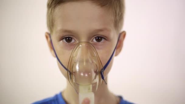 Der junge in der Maske den Inhalator behandelt