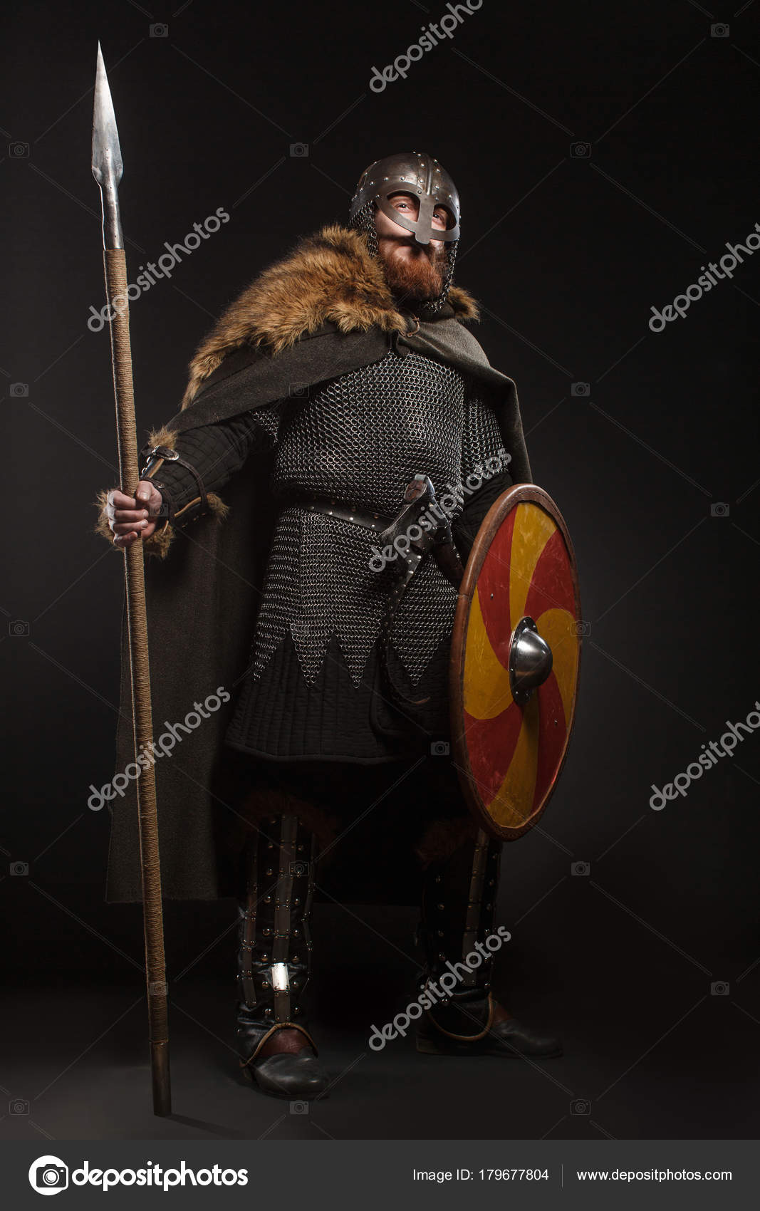 Warrior Viking in full arms with axe, shield and spear on dark b