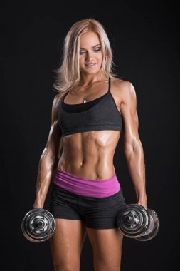 Female bodybuilder in sports clothing ready for gym exercise wit