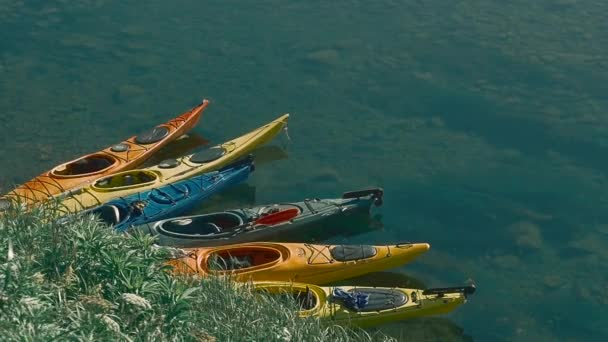 Multicolored inflatable canoes sitting on a river bank