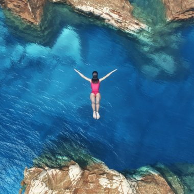 Woman jumping off cliff