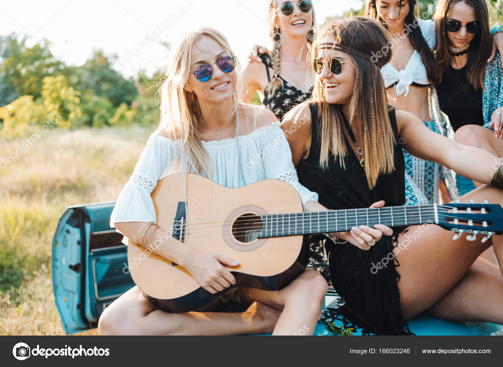 girls are sitting on the trunk with a guitar stock photo
