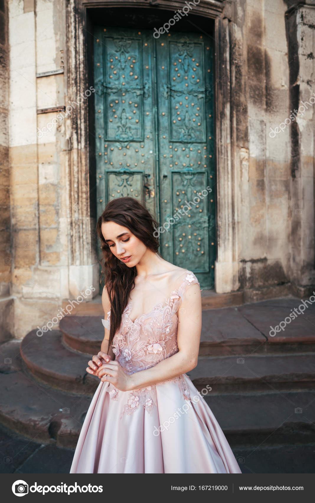 73cd9b3b1251 Μοντέλο νεαρή όμορφη γυναίκα σε ένα κομψό βραδινό φόρεμα ποζάρουν με φόντο  την πόλη από το μπαλκόνι του ένα παλιό κτίριο — Εικόνα από ...