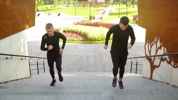 Two professional male runners, running up the staircase