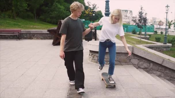 The guy is teaching his girlfriend to skateboard. Date of hipsters.