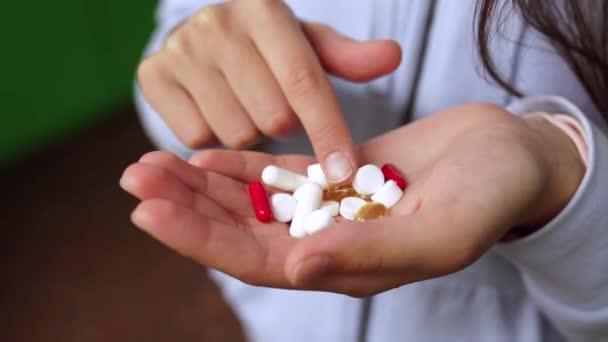 Koronavirus. Covid-19. Muž nebo žena bere a ukazuje pilulky.