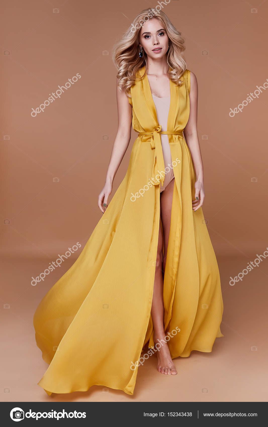 50cc0a8ea212 Ξανθά μαλλιά γυναίκα όμορφη πρόσωπο σέξι κοκαλιάρικο σώμα μαύρισμα δέρμα  φροντίδα φορούν μόδας φόρεμα μεταξιού κίτρινο χρώμα διάδρομο μοντέλο studio  στον ...