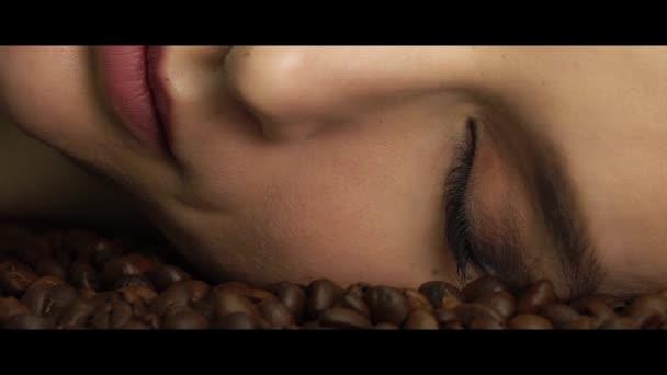 Krásná mladá sexy žena portrét světlý make-up dekorativní kosmetika pro tvář péče leží na pražená zrnková káva aromatická vůně obtéká její tvář s kouřem a chuť otevřít oči.