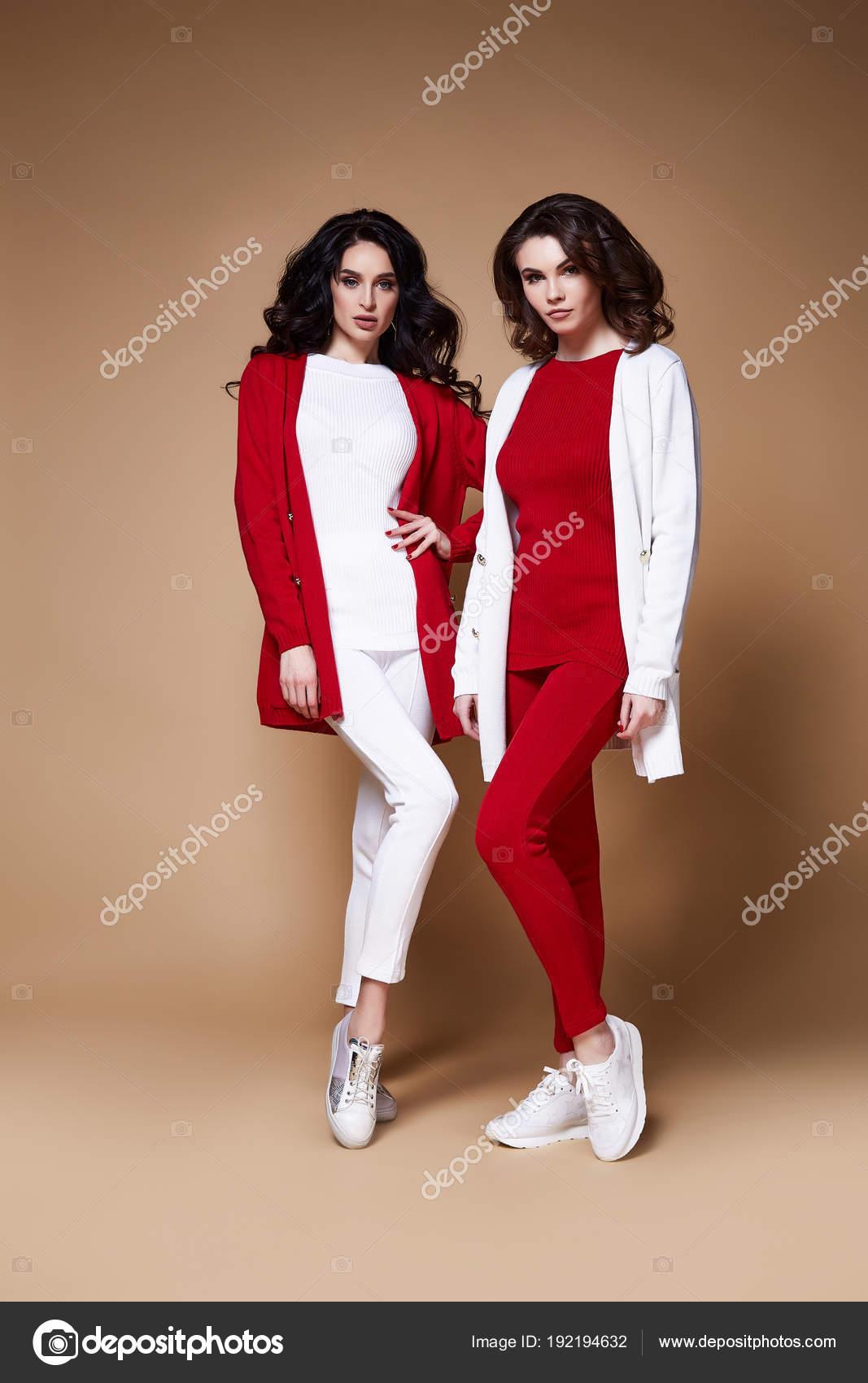 0c04e99417 Két szexi glamour divat modell nő hosszú göndör barna haj viselnek piros fehér  alkalmi ruha sportcipő és gyapjú kardigán barátom fél stílus vagy dátum ...