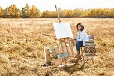 Wheat field woman artist paints a picture summer easel, beautifu
