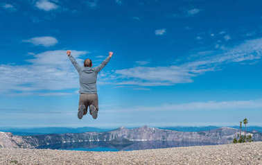 Man Jumps on Rocky Overlook to Crater Lake