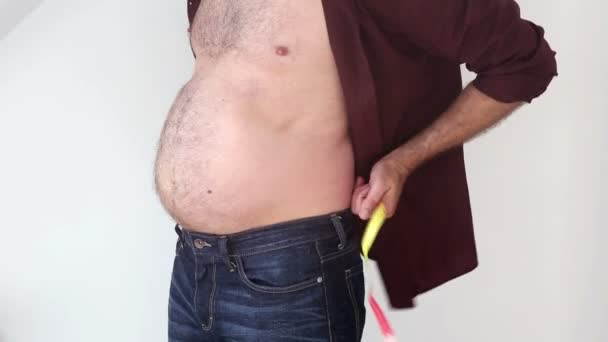 closeup of man measuring his fat belly and trying to look skinny