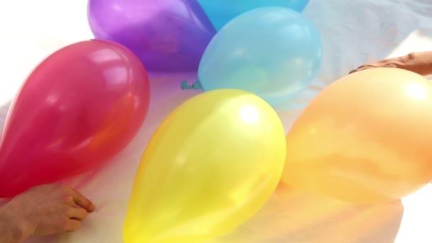 Hände von Mann und Frau Bettwäsche mit bunten Luftballons um Herzen schöpfend