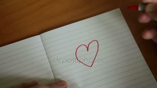 Detailní záběr na mans ruční kreslení červené srdce na papír