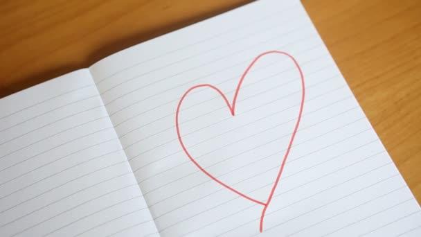 kresba velké červené srdce se objeví na bílém papíře a barevné ručně