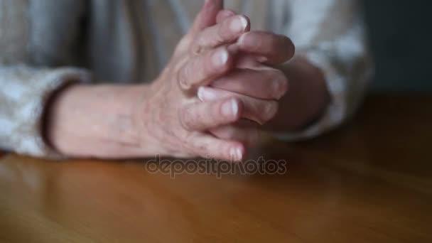 Detailní záběr na starých ženách ruce na stole pohybující se nervózně