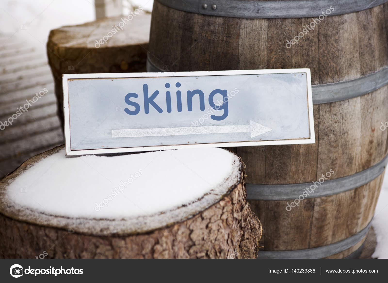 деревянный знак на дереве культи с надписью лыжи стоковое