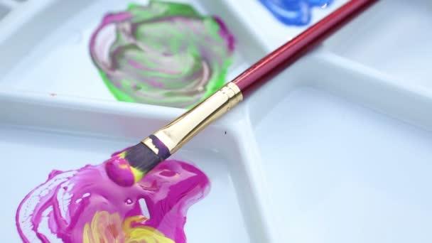 Detailní záběr na štětec a barvy s otočnou barevnou paletu