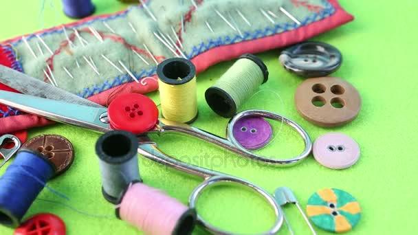 Garn, Schere, Nadeln und Knöpfe auf rotierendem grünen Tisch