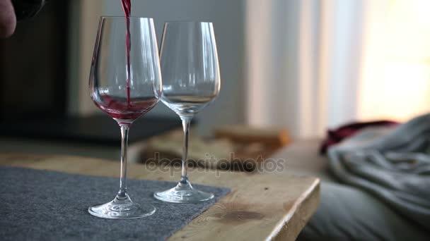 Detailní záběr rukou nalévání červeného vína ve dvě sklenice