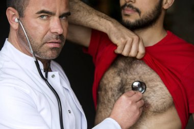 doctor with stethoscope listening to patients heartbeat