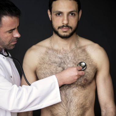doctor with stethoscope listening to shirtless patients heartbea