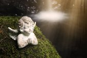 praying stone angel on moss in front of waterfall