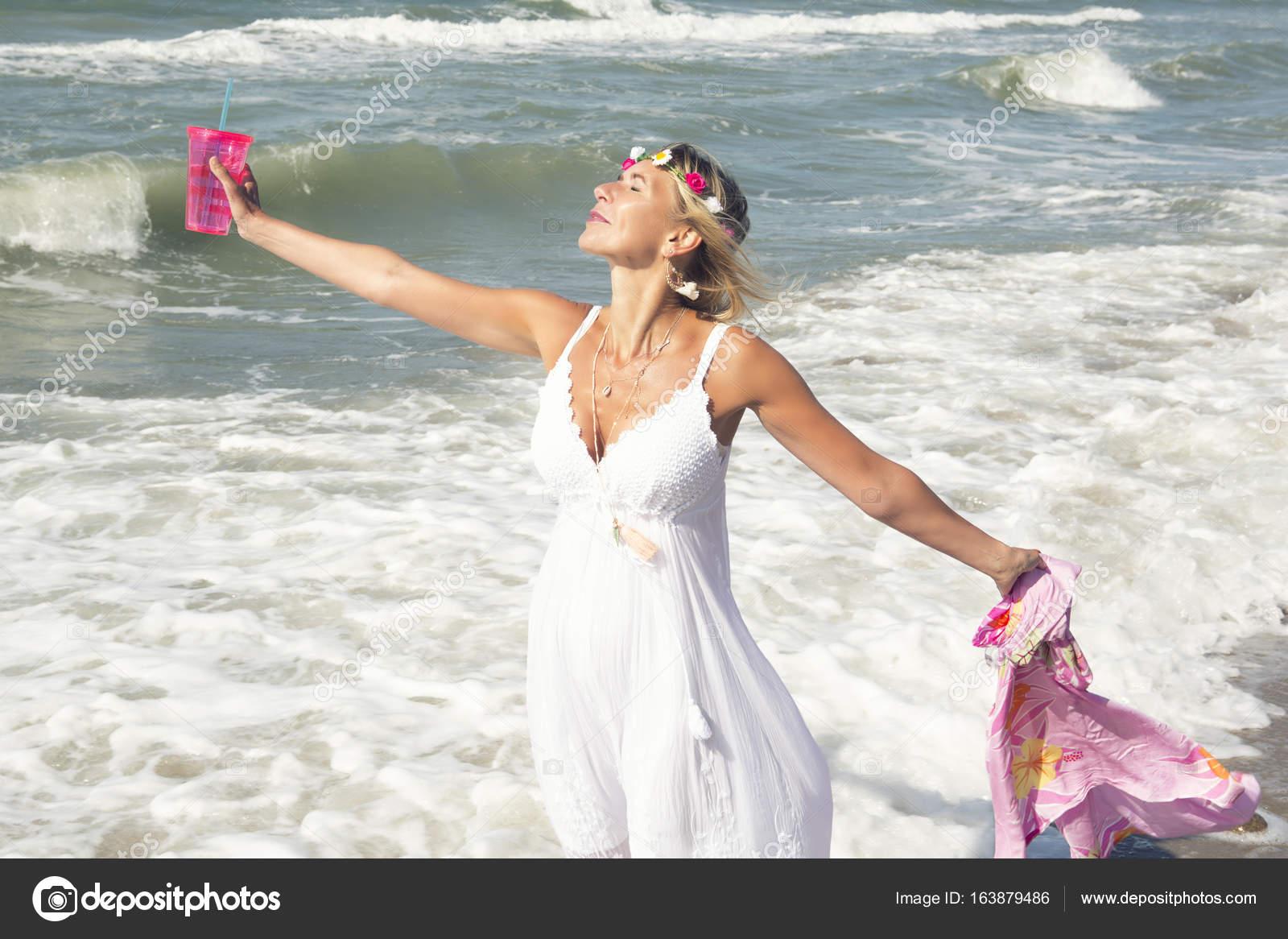 eb1635cc866d Donna bionda in vestito bianco che tiene una tazza e scialle e in piedi  sulla spiaggia — Foto di ...