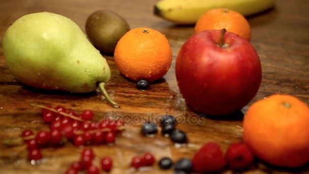 Cinemagraph čerstvého ovoce a bobule na mokré rustikální dřevěný stůl