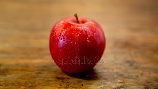 Cinemagraph of red apple with water pouring on it
