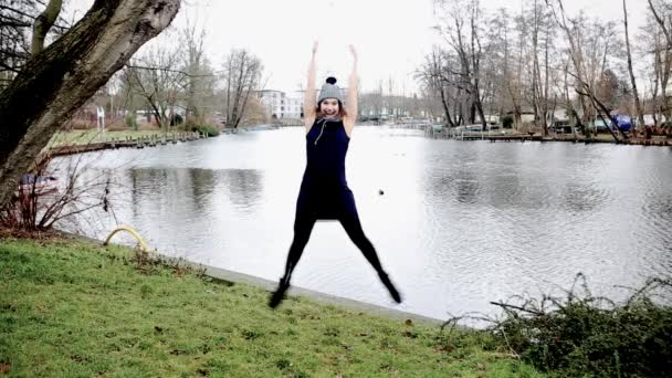 Cinemagraph of jumping young woman in front of lake