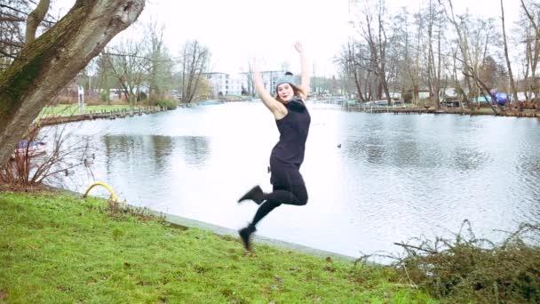Kinotag von springender junger Frau vor See