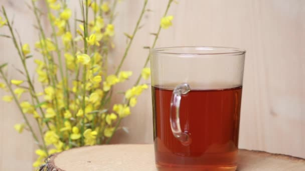 close-up of glass with hot tea on a rotating plate and yellow flowers