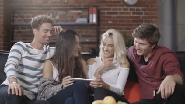 Group of happy young friends sitting on a sofa sharing a tablet computer.