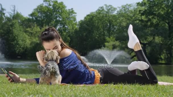 Mladá atraktivní žena ležící na rohoži a používání telefonu v sunny park
