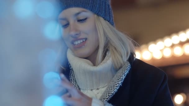 Young woman using mobile phone in a city at night.