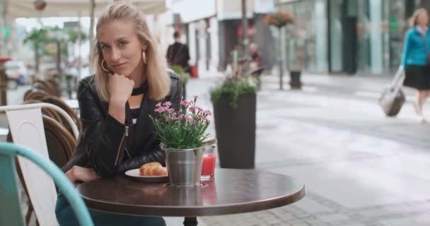 Hezká mladá kavkazské dívka sedí v kavárně a usmívá se na kameru.