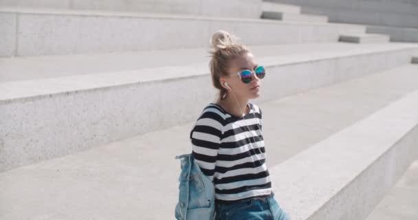 Mladá žena se sluchátky těší čas v městě.
