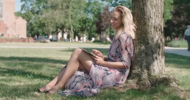 junge Frau sitzt im Park und nutzt digitales Tablet.