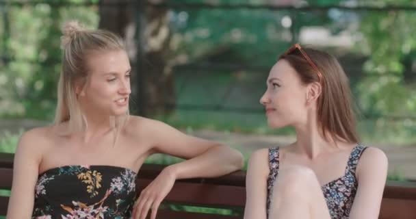 Dvě mladé dívky sedící na lavičce v parku, v létě se těší a chatování