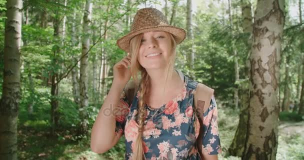 Portrait of beautiful caucasian woman in a forest wearing hat and backpack.