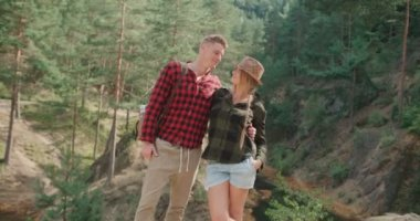 Portrait of beautiful caucasian couple spending time in a forest during sunny day.