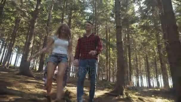 Smiling loving couple walking in woods.