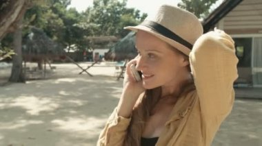 Woman talking on phone during sunny day.