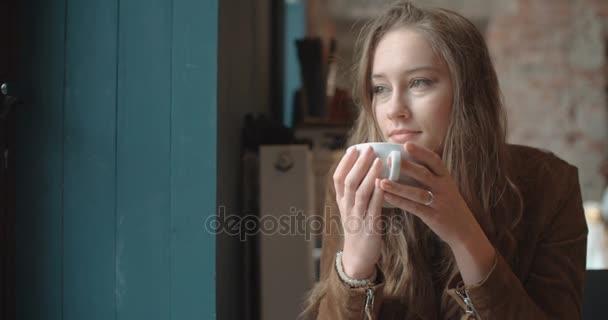 Beautiful thoughtful woman having coffee in cafe.