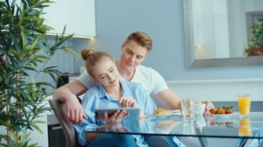 Young couple using digital tablet while having breakfast at kitchen table.