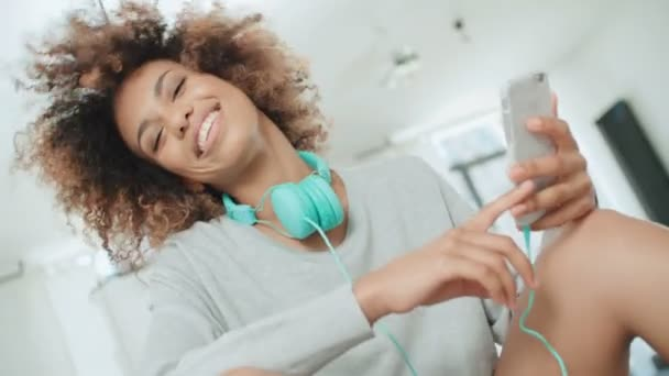 Happy and cheerful young woman enjoying music and holding phone. Beautiful young afro american woman with colorful headphones sitting on a kitchen table at home.