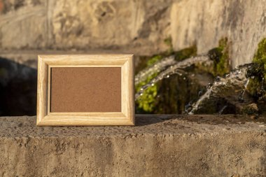 Empty Light Picture Frame Laying on Concrete Wall Near Fountain